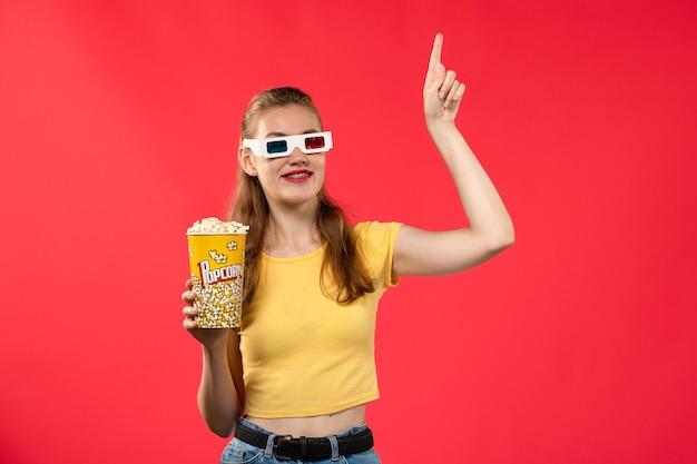 Vooraanzicht jonge vrouw bij bioscoop popcorn pakket in -d zonnebril te houden en glimlachend op rode muur bioscoop bioscoop film meisje