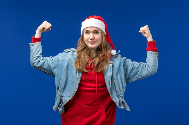 Vooraanzicht jonge vrouw buigen en glimlachen op blauwe achtergrond emotie kerstvakantie kleur