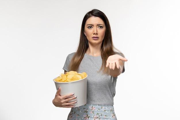 Vooraanzicht jonge vrouw cips eten en kijken naar film op het witte bureau