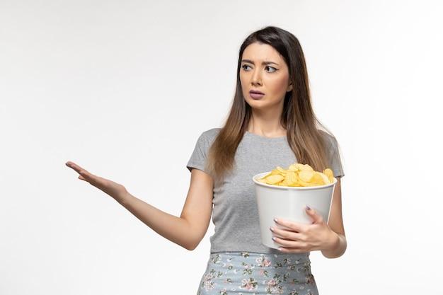 Vooraanzicht jonge vrouw cips eten en kijken naar film op wit oppervlak