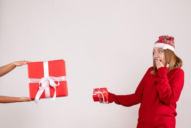 Vooraanzicht jonge vrouw die een andere kerstcadeau van de vrouw accepteert