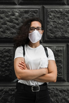 Vooraanzicht jonge vrouw die een medisch masker in openlucht draagt