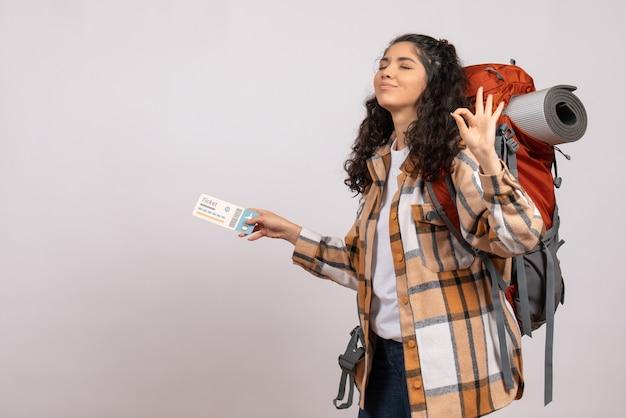 Vooraanzicht jonge vrouw die gaat wandelen met een ticket op de witte achtergrond luchttoerist bos vakantie vlucht reis campus berg