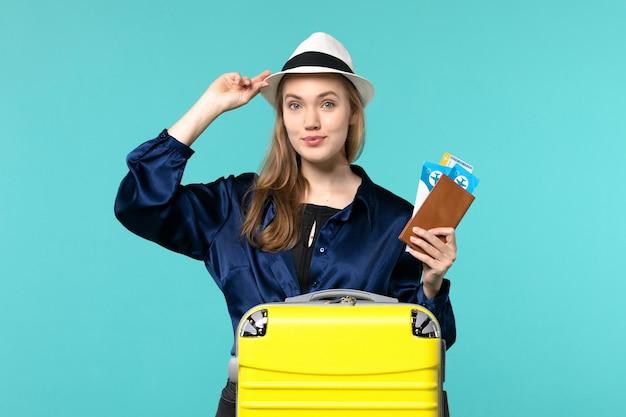 Vooraanzicht jonge vrouw die haar kaartjes houdt en voor reis op lichtblauwe achtergrond reis reis vliegtuig overzeese vakantiereizen voorbereidingen treft