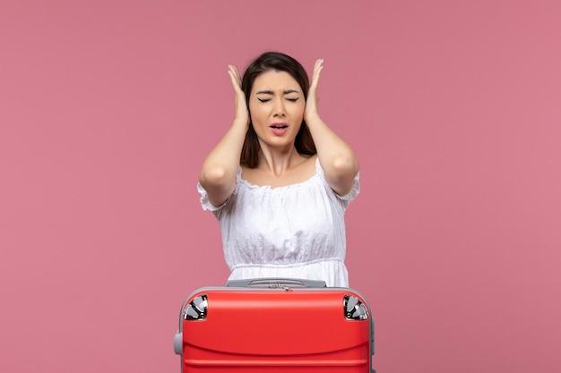 Vooraanzicht jonge vrouw die haar oren bedekt op roze achtergrond in het buitenland reis zeereis reisreis