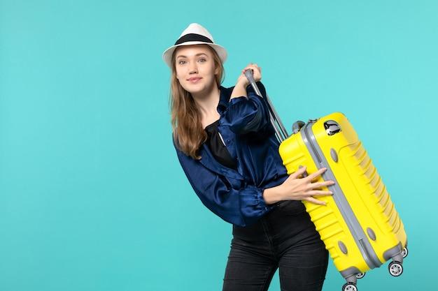 Vooraanzicht jonge vrouw die in vakantie gaat en grote zak op de blauwe achtergrondreis overzeese vakantiereis houdt