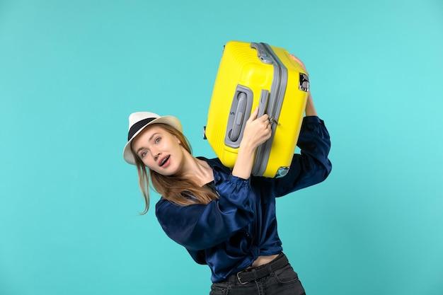 Vooraanzicht jonge vrouw die in vakantie gaat en grote zak op lichtblauwe achtergrond houdt reis overzeese reis vakantiereis