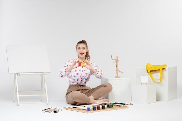Vooraanzicht jonge vrouw die kleurrijke verf vasthoudt in kleine blikjes op wit bureau trekt kleur schilder kunst vrouw kunstenaar ezel