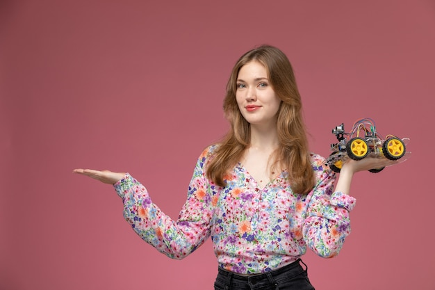 Vooraanzicht jonge vrouw die lege hand met autostuk speelgoed geeft