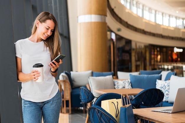 Vooraanzicht jonge vrouw die mobiele telefoon doorbladert