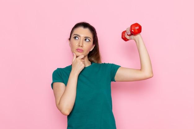 Vooraanzicht jonge vrouw die sport doet en halters op de roze muur houdt atleet sport oefent gezondheidstrainingen