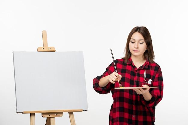 Vooraanzicht jonge vrouw die zich voorbereidt om op ezel op witte muur te schilderen