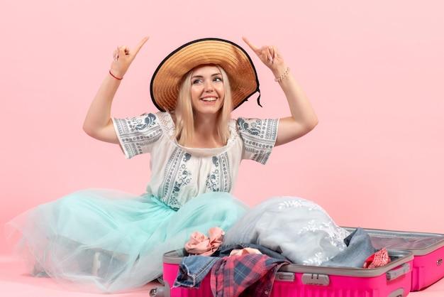 Vooraanzicht jonge vrouw die zich voorbereidt op een reis en haar kleren uit elkaar haalt op roze bureaureis, vakantie, zeevliegtuig, rustkleur