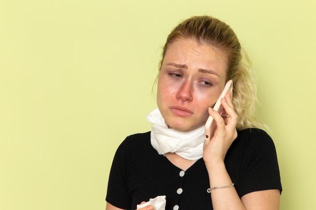 Vooraanzicht jonge vrouw erg ziek en ziek voelen praten aan de telefoon op het groene bureau ziekte geneeskunde ziekte meisje