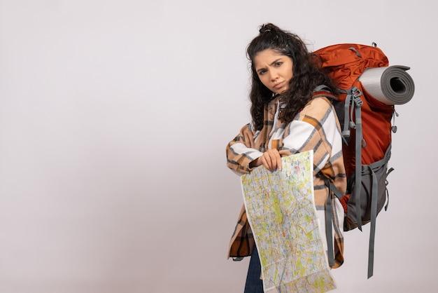 Vooraanzicht jonge vrouw gaan wandelen met kaart op witte achtergrond campus bos berg hoogte toeristische lucht
