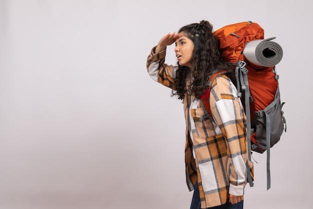 Vooraanzicht jonge vrouw gaan wandelen met rugzak kijken naar afstand op witte achtergrond campus toeristische vakantie bergreis bos lucht