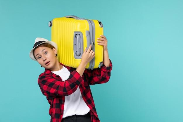Vooraanzicht jonge vrouw gaat op vakantie met haar gele tas op de lichtblauwe ruimte