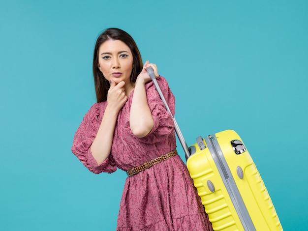 Vooraanzicht jonge vrouw gaat op vakantie met haar grote tas op lichtblauwe achtergrond reis zomer reis vrouw zee mens