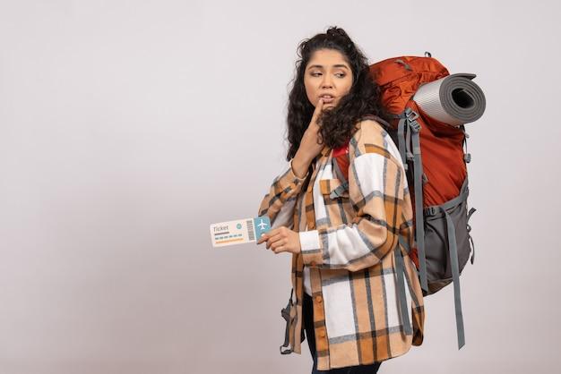 Vooraanzicht jonge vrouw gaat wandelen met ticket op de witte achtergrond reis toeristische vakantie vlucht campus lucht bergbos air