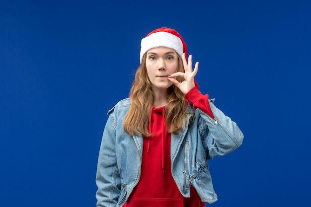 Vooraanzicht jonge vrouw haar mond sluiten op blauwe achtergrond kerst emotie kleur