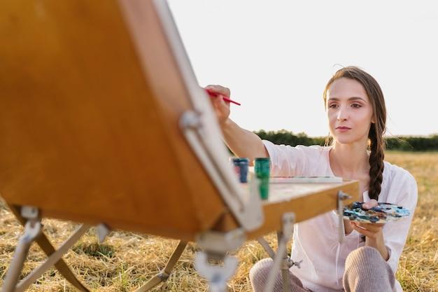 Vooraanzicht jonge vrouw hand schilderij