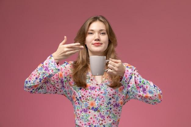 Vooraanzicht jonge vrouw houdt van geur van haar thee