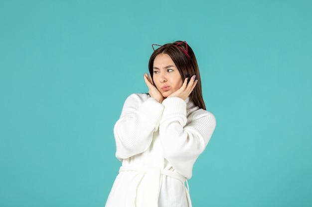 Vooraanzicht jonge vrouw in badjas en verschillende poses op blauwe achtergrond