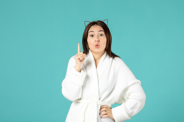 Vooraanzicht jonge vrouw in badjas heeft een idee op blauwe achtergrond