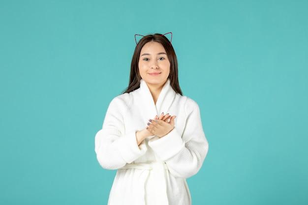 Vooraanzicht jonge vrouw in badjas klappen op blauwe achtergrond