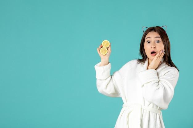 Vooraanzicht jonge vrouw in badjas met gesneden citroenen op blauwe achtergrond