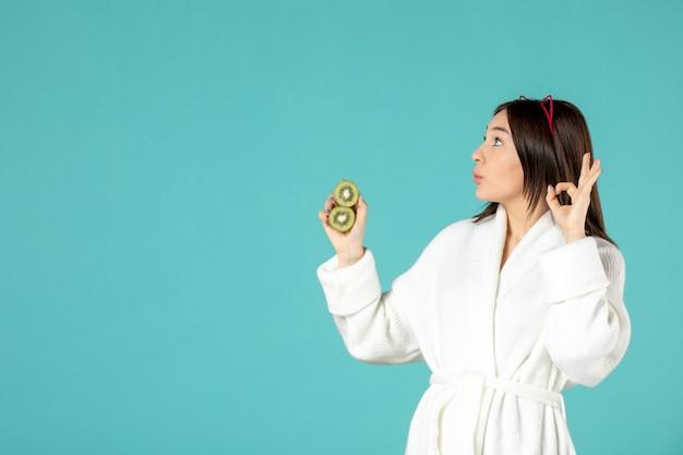 Vooraanzicht jonge vrouw in badjas met gesneden kiwi's op blauwe achtergrond