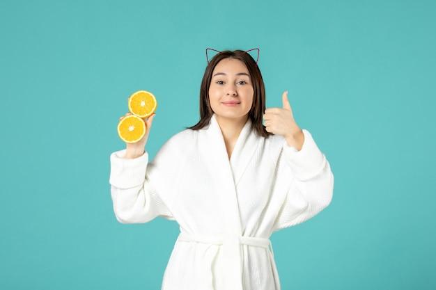 Vooraanzicht jonge vrouw in badjas met gesneden sinaasappel op blauwe achtergrond Gratis Foto