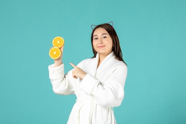 Vooraanzicht jonge vrouw in badjas met gesneden sinaasappel op blauwe achtergrond