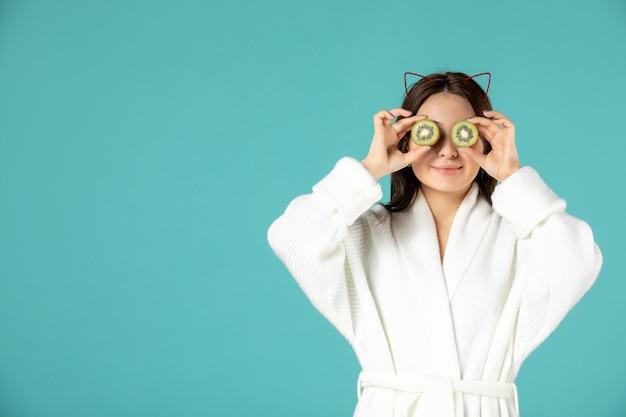 Vooraanzicht jonge vrouw in badjas met plakjes kiwi op blauwe achtergrond Gratis Foto