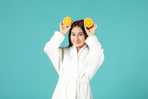 Vooraanzicht jonge vrouw in badjas met stukjes sinaasappel op blauwe achtergrond