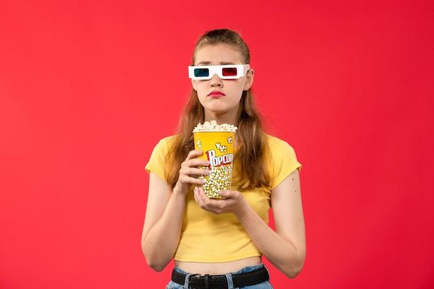 Vooraanzicht jonge vrouw in bioscoop met popcorn in d zonnebril op de rode muur bioscoop bioscoop vrouwelijke kleuren