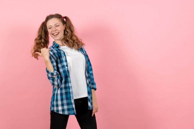 Vooraanzicht jonge vrouw in blauw geruit overhemd poseren op de roze achtergrond kind jeugd emotie model mode vrouw kleur