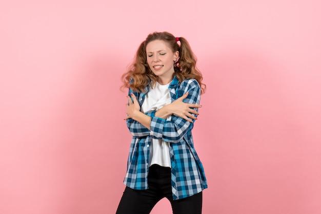 Vooraanzicht jonge vrouw in blauw geruit overhemd poseren op de roze achtergrond vrouw kind jeugd model kleur emotie