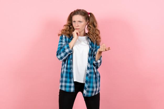 Vooraanzicht jonge vrouw in blauw geruit overhemd poseren op roze achtergrond emoties jeugd meisje model mode jongen
