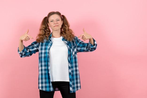 Vooraanzicht jonge vrouw in blauw geruit overhemd poseren op roze achtergrond jeugd emoties meisje jongen model mode