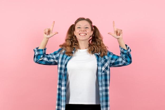 Vooraanzicht jonge vrouw in blauw geruit overhemd poseren op roze achtergrond vrouw emotie model mode meisje kleur