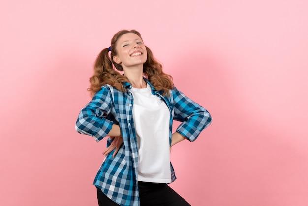 Vooraanzicht jonge vrouw in blauw geruit overhemd poseren op roze achtergrond vrouw emoties meisjes kleur model mode