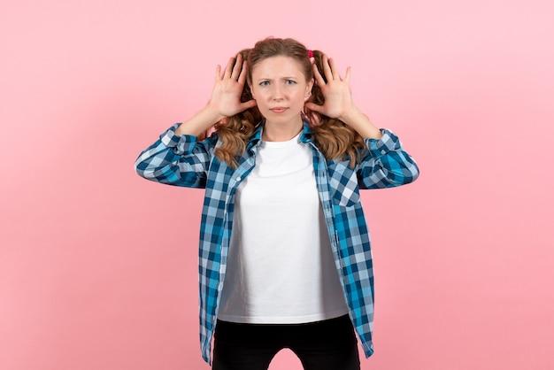 Vooraanzicht jonge vrouw in blauw geruit overhemd poseren op roze achtergrond vrouw emoties model mode meisjes kleur
