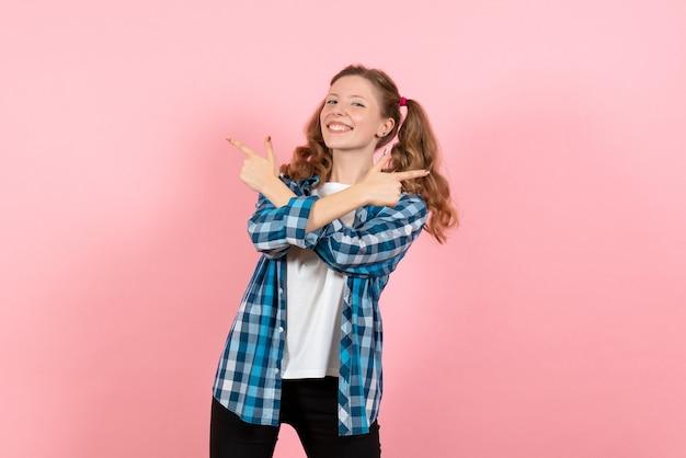 Vooraanzicht jonge vrouw in blauw geruit overhemd poseren op roze achtergrond vrouw kind jeugd model kleur emoties