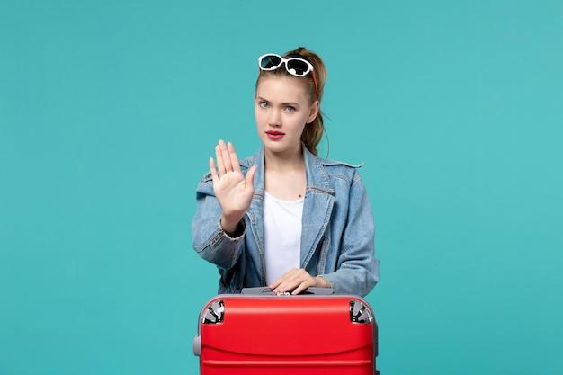 Vooraanzicht jonge vrouw in blauw jasje klaar voor reis op blauwe ruimte