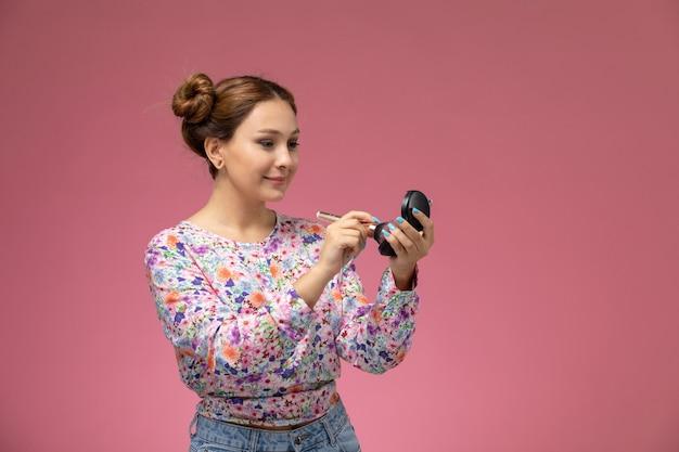 Vooraanzicht jonge vrouw in bloem ontworpen shirt en spijkerbroek glimlachend en doet een make-up op de roze achtergrond
