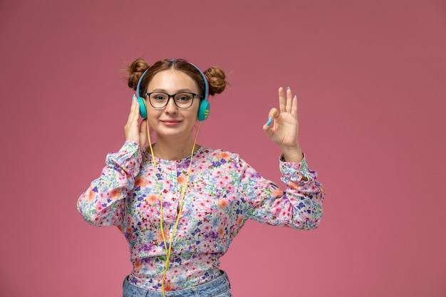 Vooraanzicht jonge vrouw in bloem ontworpen shirt en spijkerbroek luisteren naar muziek met een glimlach op de roze achtergrond