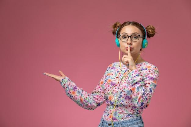 Vooraanzicht jonge vrouw in bloem ontworpen shirt en spijkerbroek luisteren naar muziek met koptelefoon op de roze achtergrond