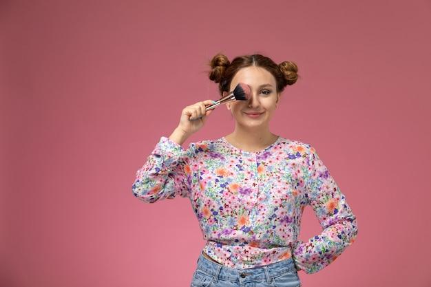 Vooraanzicht jonge vrouw in bloem ontworpen shirt en spijkerbroek met borstel en lachend op de lichte achtergrond