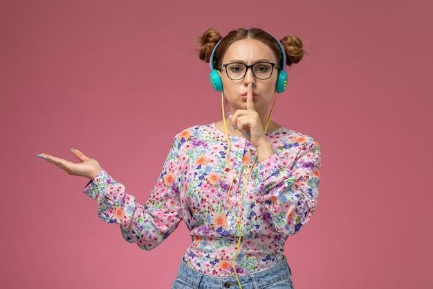 Vooraanzicht jonge vrouw in bloem ontworpen shirt en spijkerbroek poseren en luisteren naar muziek op roze achtergrond